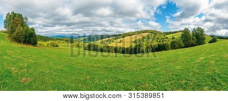 Beautiful Panorama Of A Summer Mountain Landscape. Grassy Meadow On The Hillside. Trees On The Edge