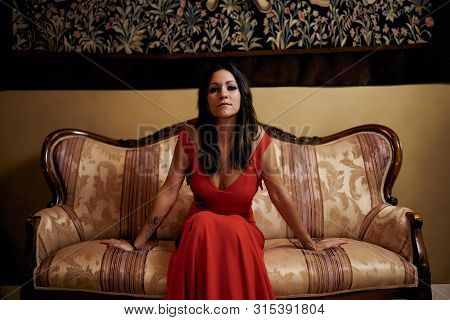 Young Brunette Woman With A Red Dress In The Living Room