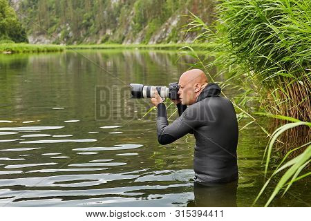 White Hairless Man In Waterproof Cloth Is Standing In River With Digital Slr Camera In His Hands And