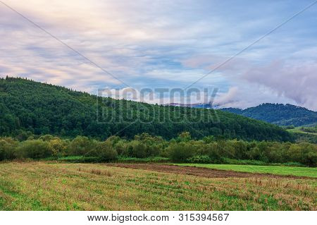 Wonderful Landscape Of Rural Area At Dawn. Amazing Cloudscape Above The Mountain Ridge.  Overcast Au