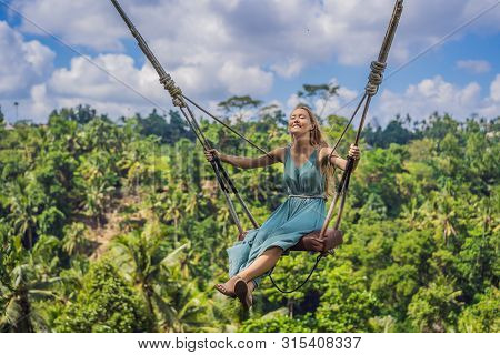 Young Woman Swinging In The Jungle Rainforest Of Bali Island, Indonesia. Swing In The Tropics. Swing