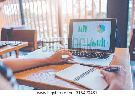 Business Woman's Hands Are Using Laptop Computers To Analyze Business Growth Chart.