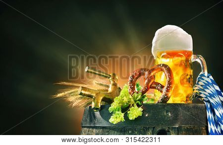 Oktoberfest background with beer stein, beer tap, pretzel, wheat and hops on a barrel
