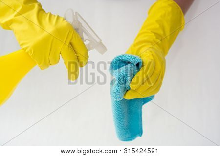 Female Hands In Yellow Rubber Gloves Hold A Spray For Cleaning Windows And Cleaning Cloth On A White