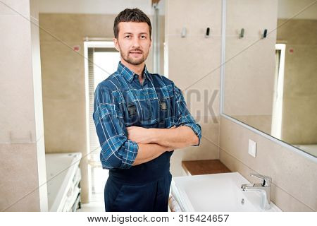 Young successful plumber in workwear standing in bathroom poster