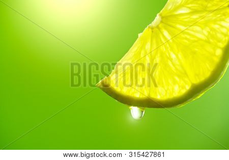 Lemon or Lime slice with drop of lemon juice close-up. Fresh and juicy Citrus over green background. Dripping lime juice closeup from sliced lemon. Lemonade. Vitamin C.