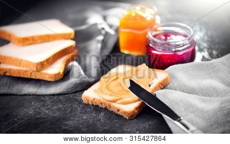 Peanut butter. Making sandwiches with Creamy smooth peanut butter and jam. Bread and peanut butter on a table with jars of jam. Natural organic vegetarian food. American cuisine