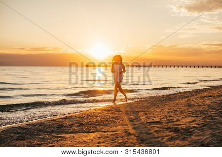Silhouette Of Young Slim Beautiful Woman On Sunset Beach. Girl Is Running In A White Dress. Late Sum