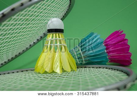 Badminton Rackets And Colorful Feathered Shuttlecocks In Blue, Yellow And Pink On Green Background I
