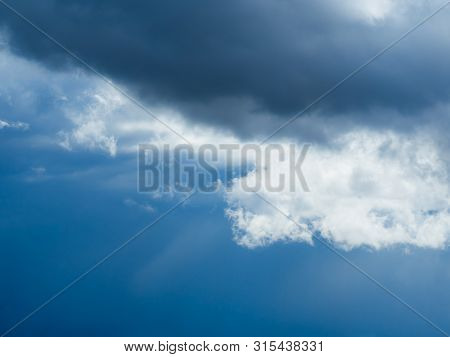 Dramatic Dark And Light Sky Clouds After A Storm With Bright Blue Sky Shining Through