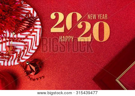Merry Christmas And Happy New Year 2020 On Red Background.top View Of Tinsel,gift Box,ball,ribbon De