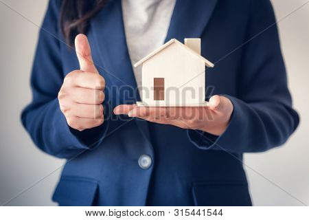 Business Property Selling and Estate Investment Concept, Close-Up of Business Woman in Suit Showing House Model With Giving Thumbs Up Against Isolated White Background., Business Real Estate Investing