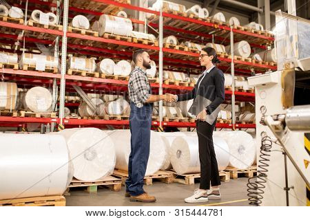 Young man and woman shaking hands after signing contract at working meeting
