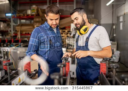Factory worker explaining his colleague how to use new industrial equipment