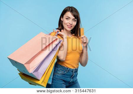Happy young shopaholic with several paperbags boasting with credit card