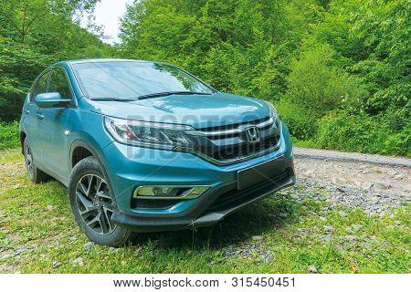 Mnt. Runa, Ukraine - Jun 22, 2019: Dirty Honda Crv Near The Old Cracked Road Through Beech Forest. 4