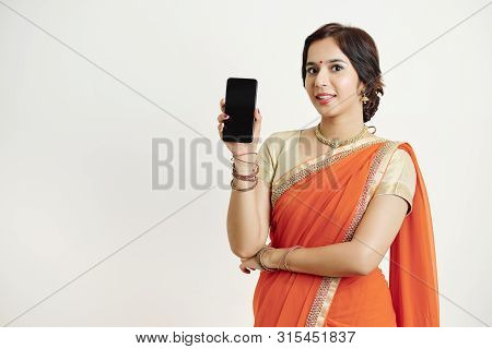 Portrait Of Young Pretty Indian Woman In Traditional Sari Showing Smartphone And Smilng At Camera, I