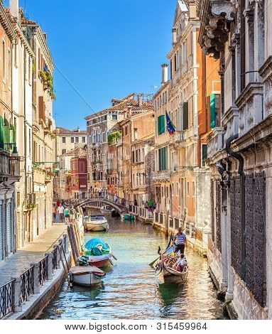 Venice, Italy - August 13, 2013: Narrow Canals With Bridge Of Venice, Italy. Tourist Sailing On An R