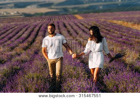 Happy Couple Holding Hands In Lavender Fields. Couple In Love On Flower Fields. Honeymoon Trip. Foll