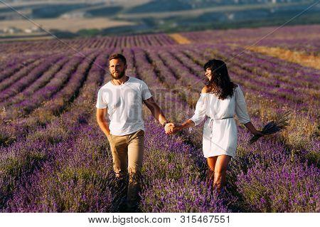 Happy Couple Holding Hands In Lavender Fields. Couple In Love On Flower Fields. Honeymoon Trip. Foll