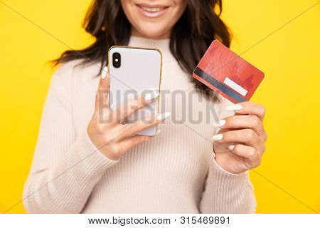Woman Using Phone And Credit Card Isolated At The Yellow Background.