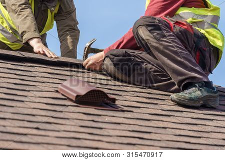 Two Mature Roofers In Protective Uniform Using Helmet And Installing Asphalt Shingle Or Roof Tile On