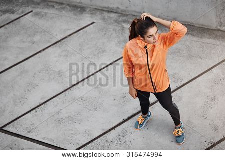 Sport, Urban Lifestyle And Recreation Concept. Upper View Fit And Appealing Sportswoman In Orange Ru