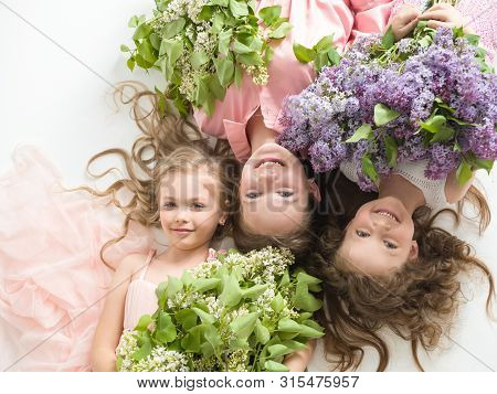 Portrait Of Three Beautiful Girls With Lilacs In Their Hands