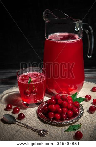Cherry Juice In A Glass. Garnished With Cherries. Dark Wooden Background. Next To A Glass Is A Metal