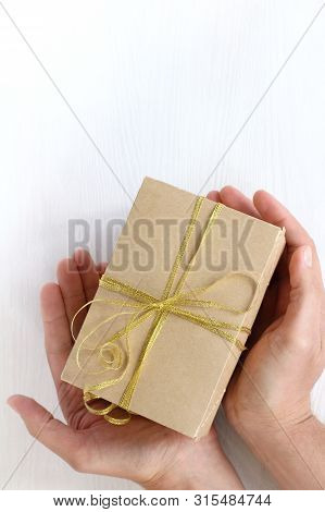 Box With A Bow In Hands Over A Light Surface Top View / Gift Giving