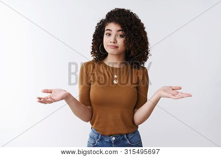 Not Big Deal. Unbothered Careless Stylish Young Modern Female Curly Dark Hair Shrugging Hands Spread