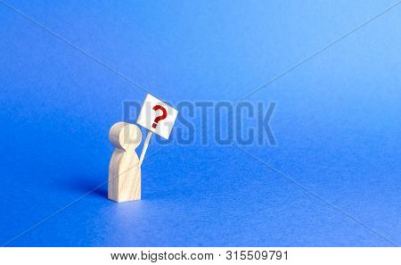A Person Figurine With A Question Mark. Minimalism. Asking, Searching For Truth And Demanding Truth.