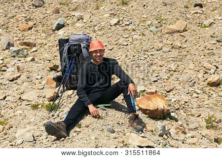 Hiker In The Mountains On Halt. Climber With Backpack