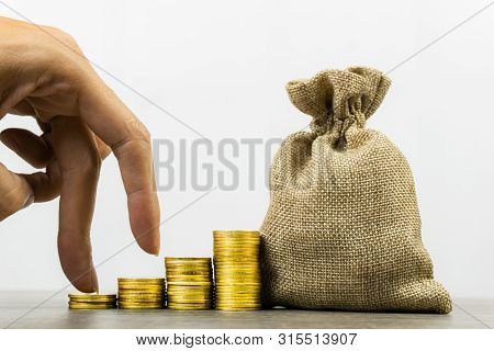 Savings Money. Money Investment. A Businessman Hand On Stack Of Coins With Money Bag On Wood Table O