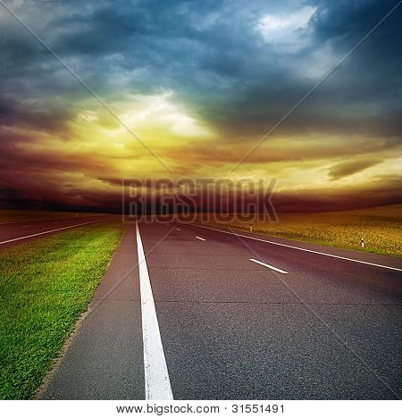 Asphalt Road In The Field Over Stormy Sky