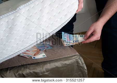 Man Putting Money Under His Mattress To Save It. Showing No Trust In Financial Institutions And Bank