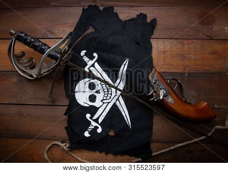Pirate Flag Jolly Roger Sword And Pistol Lying On A Dark Wooden Surface