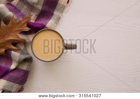 Autumn Concept. A Cup Of Warm Cocoa, Dried Leaves And Woolen Scard Of White Background. Copy Space.
