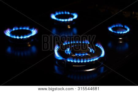 Four Blue Flames Of Natural Gas Stove In The Dark