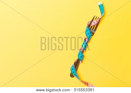 Diet And Healthy Eating Concept With Wrapped Fork In Measuring Tape On Yellow Background. Top View O
