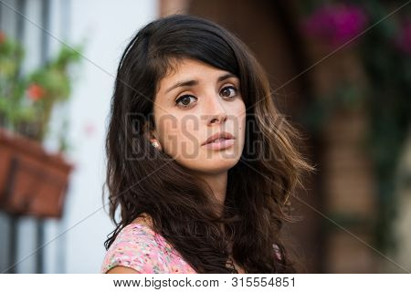 A Portrait Of A Young Woman In A Tipical Spanish Yard Looking Into The Camera.