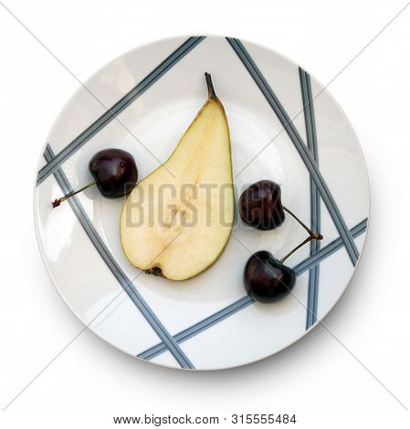 Still Life With Half Of Sweet Ripe Pear And Wild Cherries On The Beautiful Plate Against White Backg