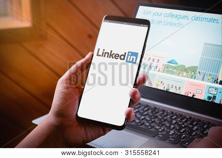 Bangkok, Thailand - August 5, 2019: Hands Holding Smartphone With Linkedin Logo On Screen And Linked