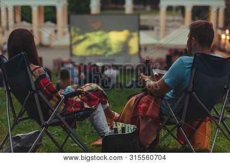 Couple Sitting In Camp-chairs In City Park Looking Movie Outdoors At Open Air Cinema Lifestyle