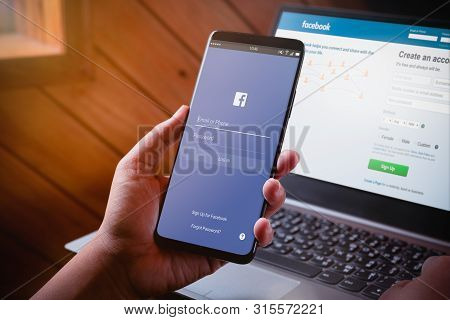 Bangkok, Thailand - August 5, 2019: Hands Holding Smartphone With Facebook Log On Screen And Faceboo
