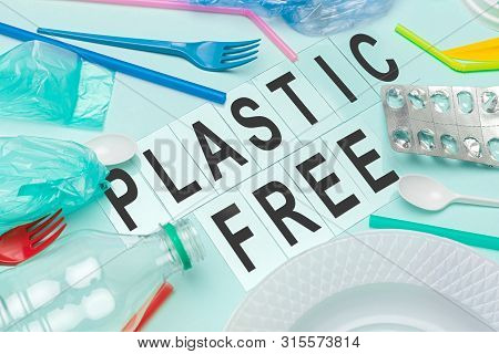 Piece of discarded garbage placed around words Plastic free on blue background poster
