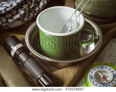 Traditional tourist equipment kit on khaki textile background poster
