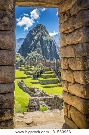 The Inca Ruins Of Machu Picchu, Unesco World Heritage Site Through The Frame Of Stone Wall