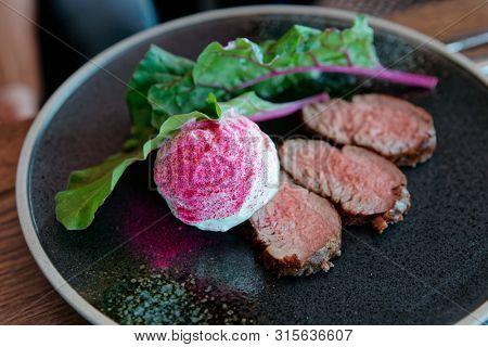 Roast beef with creamy horse-radish sauce on plate