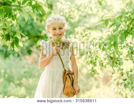 Cute little girl is walking between the trees, holding bag and flower, in green park